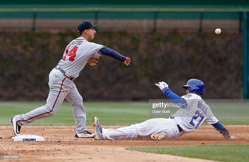 Daniel Castro #14 of the Atlanta Braves turns a double play past <a gi-track='captionPersonalityLinkClicked' href=/galleries/search?phrase=Addison+Russell&family=editorial&specificpeople=9513105 ng-click='$event.stopPropagation()'>Addison Russell</a> #27 of the Chicago Cubs in the seventh inning at Wrigley Field on April 29, 2016 in Chicago, Illinois.