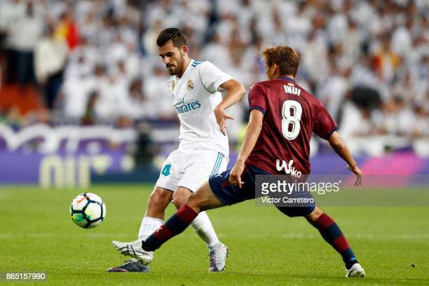 Daniel Ceballos of Real Madrid competes for the ball with Takashi Inui of Eibar during the La Liga match between Real Madrid and Eibar at Estadio...