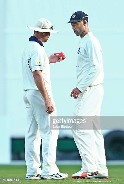 Daniel Christian and Rob Quiney of Victoria inspect the condition of the pink ball during day one of the Sheffield Shield match between Victoria and...