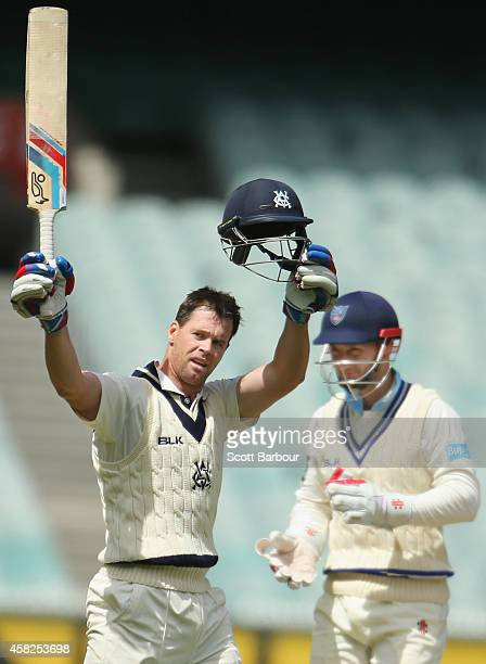 Daniel Christian of Victoria celebrates reaching his century as wicketkeeper Peter Nevill of New South Wales looks on during day three of the...