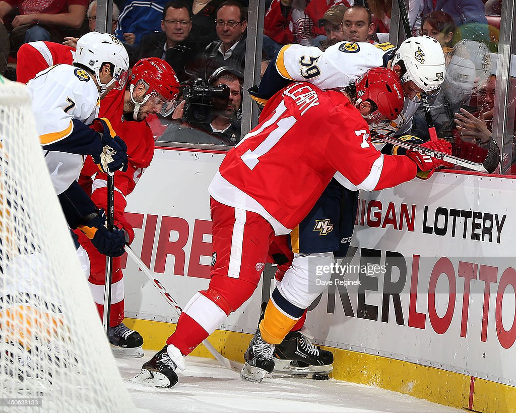 Daniel Cleary #71 and Drew Miller #20 of the Detroit Red Wings battle for the puck behind the net with Roman Josi #59 and Matt Cullen #7 of the Nashville Predators during an NHL game at Joe Louis Arena on November 19, 2013 in Detroit, Michigan.
