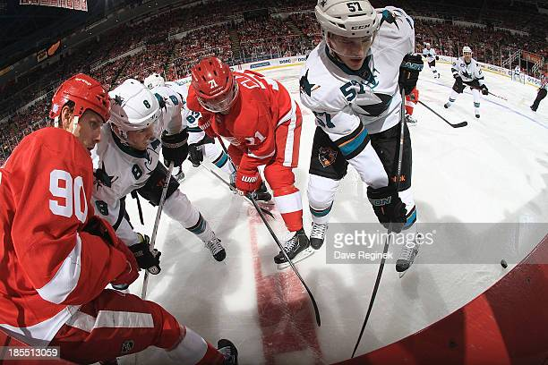 Daniel Cleary and Stephen Weiss of the Detroit Red Wings battle for the puck along the boards with Tommy Wingels and Joe Pavelski of the San Jose...