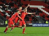 Daniel Cleary of Liverpool celebrates his goal with team mates Tom Brewitt and Sergi Canos during the UEFA Youth League fixture between Liverpool and...