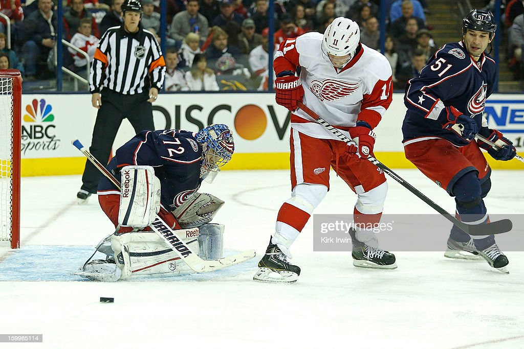 Daniel Cleary #11 of the Detroit Red Wings attempts to set a screen as Sergei Bobrovsky #72 of the Columbus Blue Jackets makes a save and Fedor Tyutin #51 of the Columbus Blue Jackets looks for the rebound on January 21, 2013 at Nationwide Arena in Columbus, Ohio.
