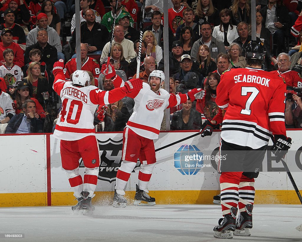 Daniel Cleary #11 of the Detroit Red Wings celebrates his goal with teammate Henrik Zetterberg #40 as Brent Seabrook #7 of the Chicago Blackhawks skates away during Game Five of the Western Conference Semifinals during the 2013 NHL Stanley Cup Playoffs at United Center on May 25, 2013 in Chicago, Illinois.
