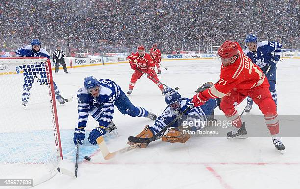 Daniel Cleary of the Detroit Red Wings centers the puck as Carl Gunnarsson and goaltender Jonathan Bernier of the Toronto Maple Leafs try to defend...