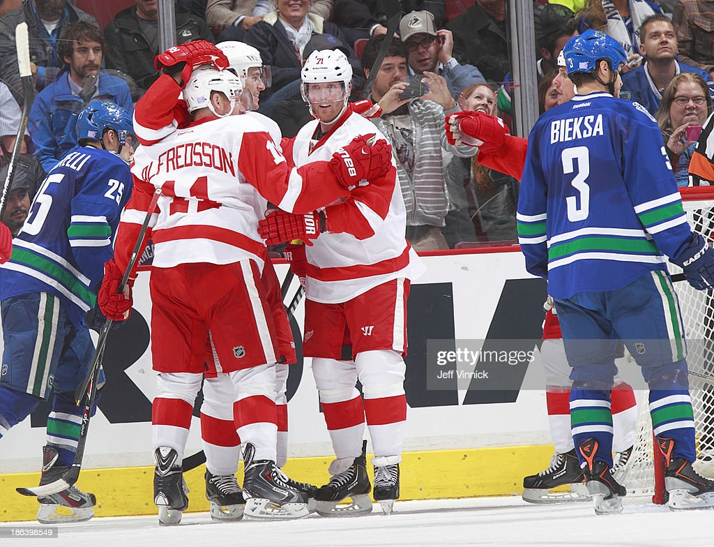<a gi-track='captionPersonalityLinkClicked' href=/galleries/search?phrase=Daniel+Cleary&family=editorial&specificpeople=220490 ng-click='$event.stopPropagation()'>Daniel Cleary</a> #71 of the Detroit Red Wings congratulates goals scorer <a gi-track='captionPersonalityLinkClicked' href=/galleries/search?phrase=Daniel+Alfredsson&family=editorial&specificpeople=201853 ng-click='$event.stopPropagation()'>Daniel Alfredsson</a> #11 while <a gi-track='captionPersonalityLinkClicked' href=/galleries/search?phrase=Kevin+Bieksa&family=editorial&specificpeople=688792 ng-click='$event.stopPropagation()'>Kevin Bieksa</a> #3 and <a gi-track='captionPersonalityLinkClicked' href=/galleries/search?phrase=Mike+Santorelli&family=editorial&specificpeople=4517042 ng-click='$event.stopPropagation()'>Mike Santorelli</a> #25 of the Vancouver Canucks skate away during their NHL game at Rogers Arena on October 30, 2013 in Vancouver, British Columbia, Canada.