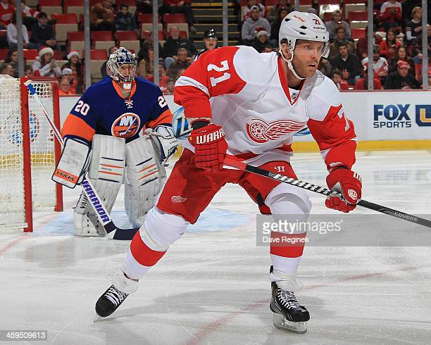 Daniel Cleary of the Detroit Red Wings follows the play in front of Evgeni Nabokov of the New York Islanders during an NHL game at Joe Louis Arena on...