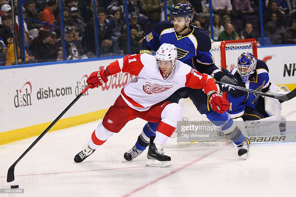 Daniel Cleary of the Detroit Red Wings holds Carlo Colaiacovo of the St Louis Blues off the puck at the Scottrade Center on December 6 2011 in St...