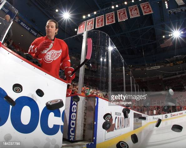 Daniel Cleary of the Detroit Red Wings knocks the pucks onto the ice for warm ups before a NHL game against the Philadelphia Flyers at Joe Louis...