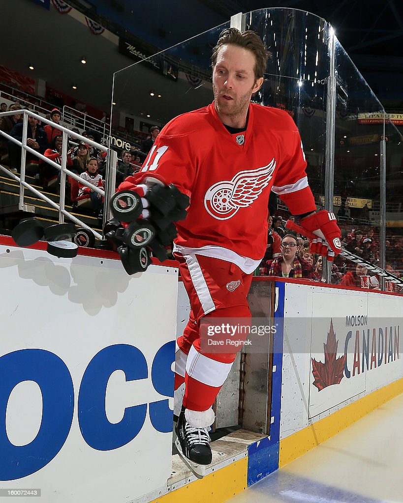 Daniel Cleary #11 of the Detroit Red Wings pushes the pucks on the ice for pre game warm ups before an NHL game against the Minnesota Wild at Joe Louis Arena on January 25, 2013 in Detroit, Michigan.
