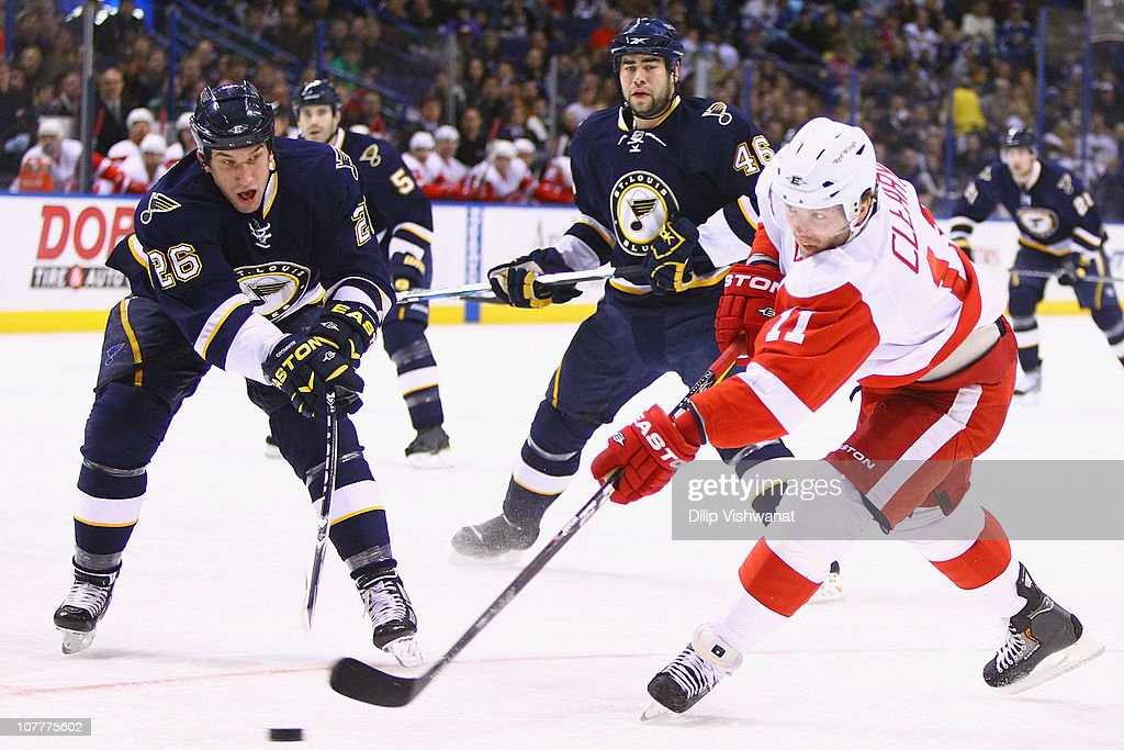 <a gi-track='captionPersonalityLinkClicked' href=/galleries/search?phrase=Daniel+Cleary&family=editorial&specificpeople=220490 ng-click='$event.stopPropagation()'>Daniel Cleary</a> #11 of the Detroit Red Wings shoots the puck against <a gi-track='captionPersonalityLinkClicked' href=/galleries/search?phrase=B.J.+Crombeen&family=editorial&specificpeople=4505846 ng-click='$event.stopPropagation()'>B.J. Crombeen</a> #26 of the St. Louis Blues at the Scottrade Center on December 23, 2010 in St. Louis, Missouri.