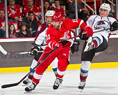 Daniel Cleary of the Detroit Red Wings skates up ice fighting thru a stick check from Tyson Barrie of the Colorado Avalanche during a NHL game on...