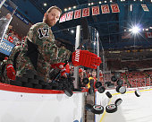 Daniel Cleary of the Detroit Red Wings smacks the pucks to the ice for warmups while wearing his 'Camo' jersey in honor of the servicemen and women...