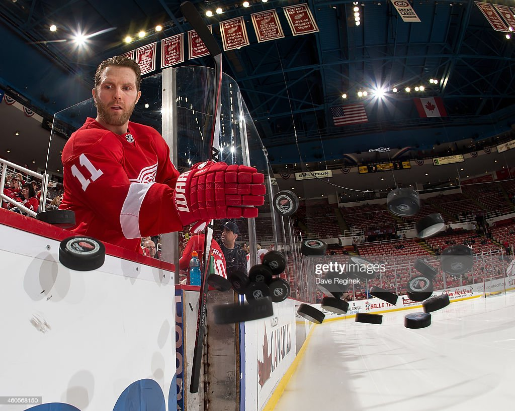 Daniel Cleary of the Detroit Red Wings smacks the pucks to the ice for warmups before a NHL game against the Columbus Blue Jackets on December 16...