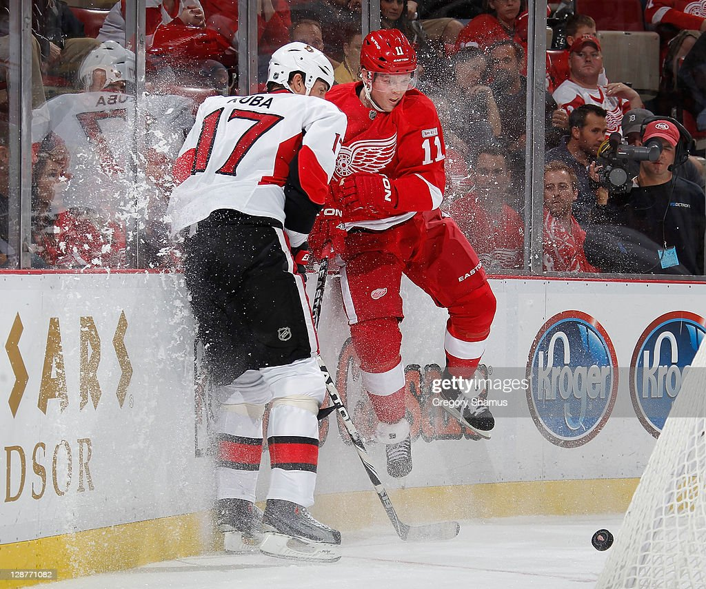 <a gi-track='captionPersonalityLinkClicked' href=/galleries/search?phrase=Daniel+Cleary&family=editorial&specificpeople=220490 ng-click='$event.stopPropagation()'>Daniel Cleary</a> #11 of the Detroit Red Wings takes a check from <a gi-track='captionPersonalityLinkClicked' href=/galleries/search?phrase=Filip+Kuba&family=editorial&specificpeople=209425 ng-click='$event.stopPropagation()'>Filip Kuba</a> #17 of the Ottawa Senators at Joe Louis Arena on October 7, 2011 in Detroit, Michigan.