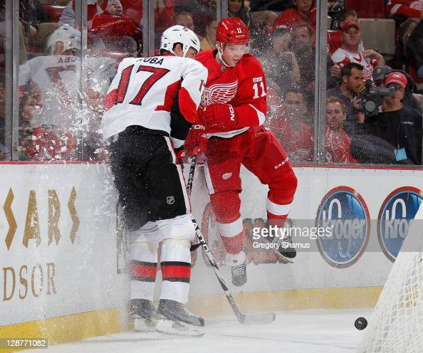 Daniel Cleary of the Detroit Red Wings takes a check from Filip Kuba of the Ottawa Senators at Joe Louis Arena on October 7 2011 in Detroit Michigan