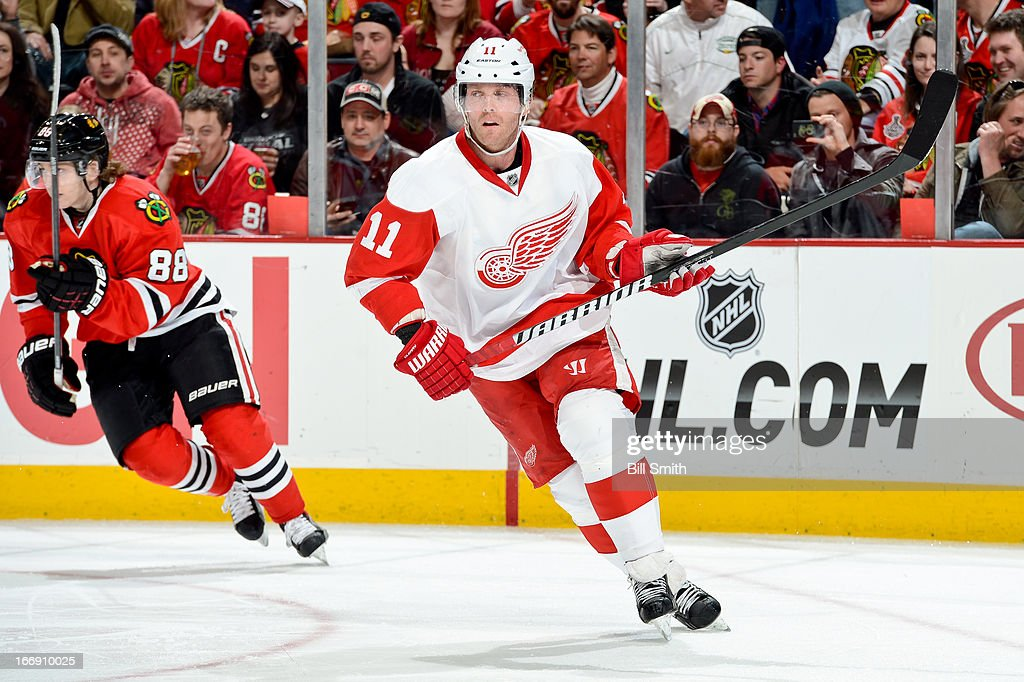 <a gi-track='captionPersonalityLinkClicked' href=/galleries/search?phrase=Daniel+Cleary&family=editorial&specificpeople=220490 ng-click='$event.stopPropagation()'>Daniel Cleary</a> #11 of the Detroit Red Wings watches for the puck as Patrick Kane #88 of the Chicago Blackhawks skates in the background during the NHL game on April 12, 2013 at the United Center in Chicago, Illinois.