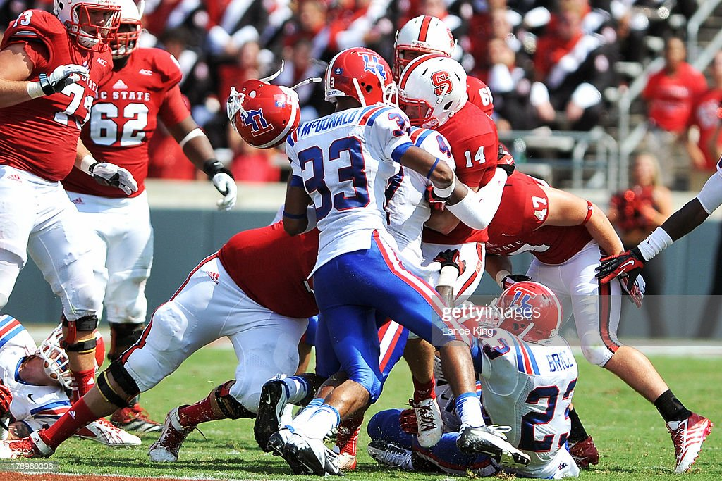 Daniel Cobb #47 of the Louisiana Tech Bulldogs loses his helmet while making a tackle on Bryant Shirreffs #14 of the North Carolina State Wolfpack at Carter-Finley Stadium on August 31, 2013 in Raleigh, North Carolina.