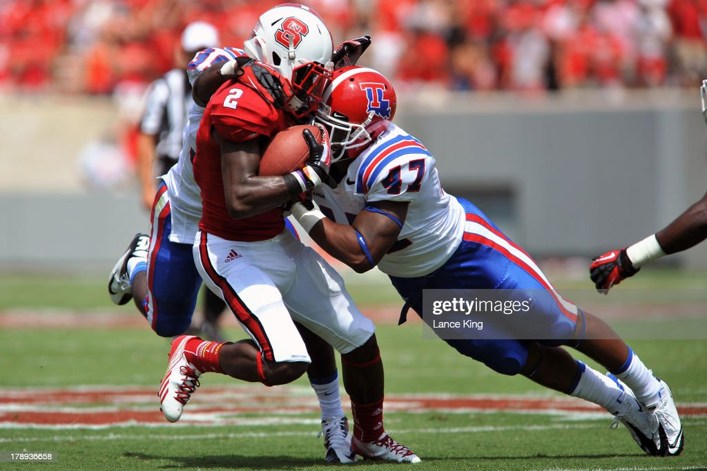 Daniel Cobb #47 of the Louisiana Tech Bulldogs tackles Rashard Smith #2 of the North Carolina State Wolfpack at Carter-Finley Stadium on August 31, 2013 in Raleigh, North Carolina.