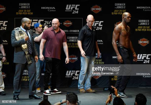 Daniel Cormier holding the UFC belt looks at Jon Jones as he walks away after a face off with Dana White UFC President looking on during the UFC 214...