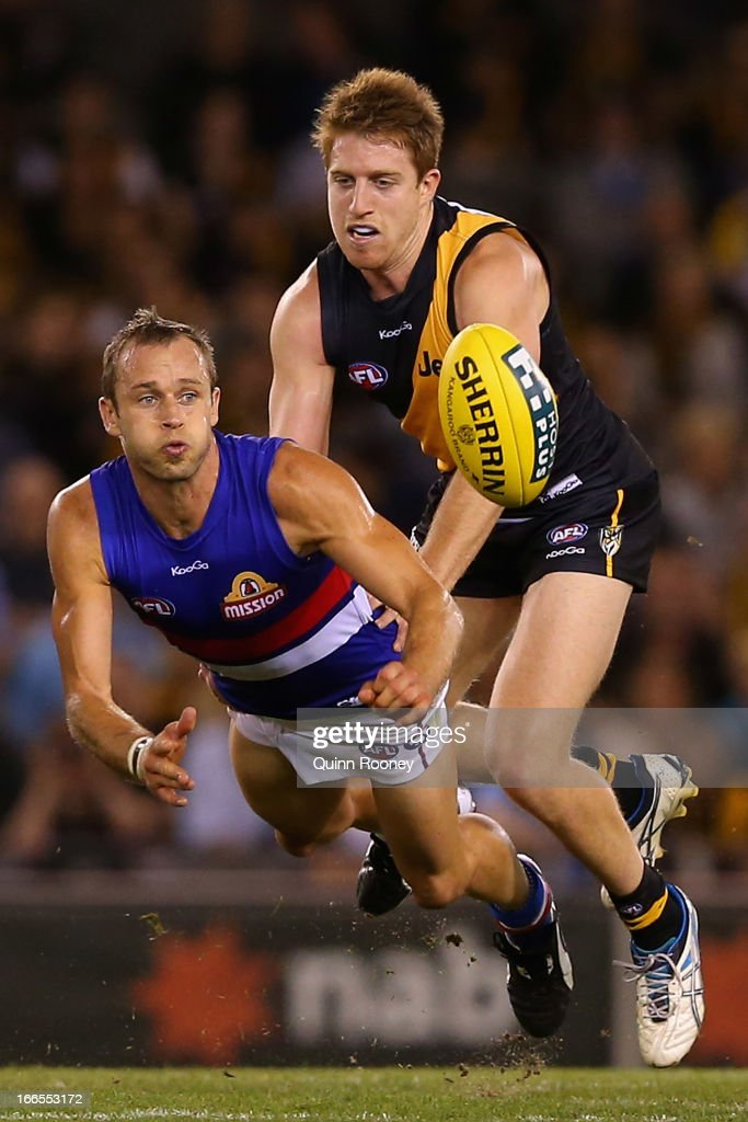 Daniel Cross of the Bulldogs handballs whilst being tackled by Reece Conca of the Tigers during the round three AFL match between the Richmond Tigers and the Western Bulldogs at Etihad Stadium on April 14, 2013 in Melbourne, Australia.