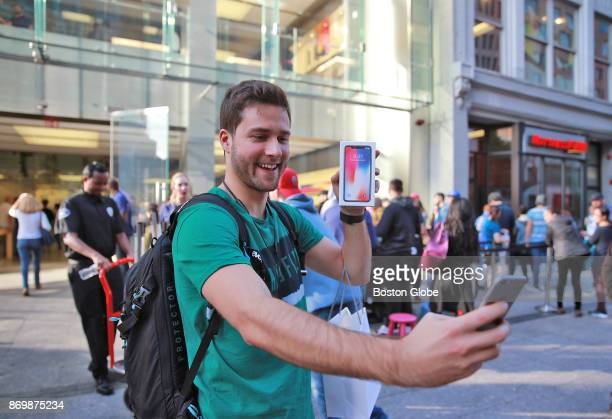 Daniel Csonch from London England takes a selfie using his old iPhone as he holds the newlyreleased iPhone X in front of the Boylston Street Apple...