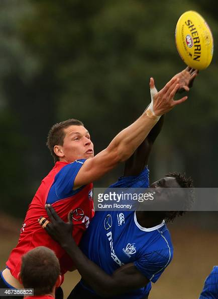 Daniel Currie and Majak Daw of the Kangaroos compete in the ruck during a North Melbourne Kangaroos AFL training session at Arden Street Oval on...