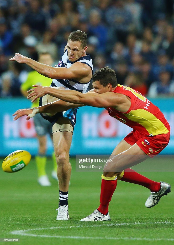 Daniel Currie of the Suns smothers the kick of Joel Selwood of the Cats during the round six AFL match between the Geelong Cats and the Gold Coast Suns at Simonds Stadium on April 30, 2016 in Geelong, Australia.