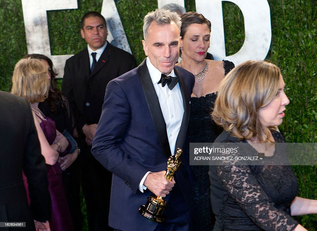 Daniel Day Lewis carrying his Oscar for best actor arrives for the 2013 Vanity Fair Oscar Party on February 24, 2013 in Hollywood, California.