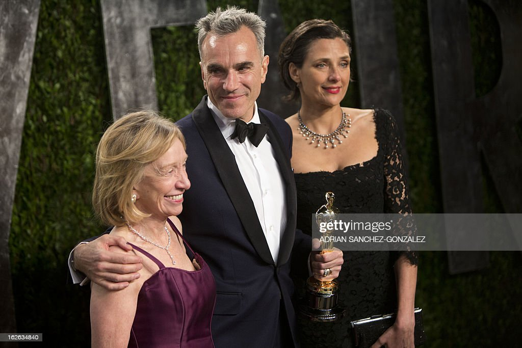 Daniel Day Lewis (C) carrying his Oscar for best actor arrives for the 2013 Vanity Fair Oscar Party on February 24, 2013 in Hollywood, California.