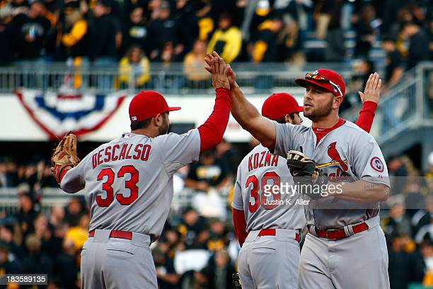 Daniel Descalso and Matt Holliday of the St Louis Cardinals celebrate defeating the Pittsburgh Pirates in Game Four of the National League Division...