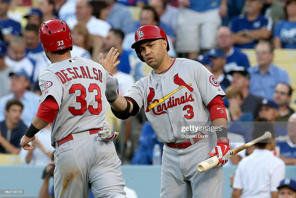 <a gi-track='captionPersonalityLinkClicked' href=/galleries/search?phrase=Daniel+Descalso&family=editorial&specificpeople=6800752 ng-click='$event.stopPropagation()'>Daniel Descalso</a> #33 celebrates with <a gi-track='captionPersonalityLinkClicked' href=/galleries/search?phrase=Carlos+Beltran&family=editorial&specificpeople=167108 ng-click='$event.stopPropagation()'>Carlos Beltran</a> #3 of the St. Louis Cardinals after Descalso scores in the third inning against the Los Angeles Dodgers in Game Four of the National League Championship Series at Dodger Stadium on October 15, 2013 in Los Angeles, California.