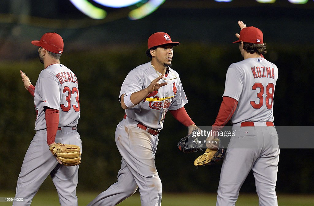 Daniel Descalso #33 (L-R), Jon Jay #19 and Pete Kozma #38 of the St. Louis Cardinals celebrate their win over the Chicago Cubs at Wrigley Field on September 22, 2014 in Chicago, Illinois. The Cardinals defeated the Cubs 8-0.