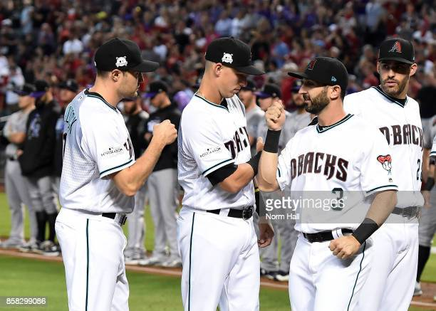 Daniel Descalso of the Arizona Diamondbacks high fives teammates Jake Lamb and AJ Pollock prior to the start of the National League Wild Card Game...