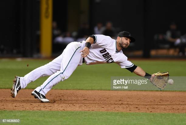 Daniel Descalso of the Arizona Diamondbacks makes a diving stop on a ground ball during the sixth inning against the Colorado Rockies at Chase Field...