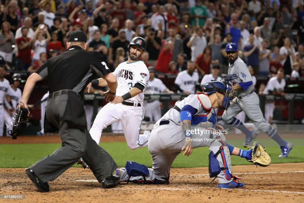 Daniel Descalso #3 of the Arizona Diamondbacks slides in to score a run past catcher Yasmani Grandal #9 of the Los Angeles Dodgers during the eighth inning of the MLB game at Chase Field on April 21, 2017 in Phoenix, Arizona. The Diamondbacks defeated the Dodgers 13-5.