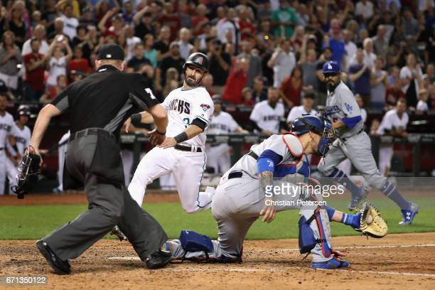 Daniel Descalso of the Arizona Diamondbacks slides in to score a run past catcher Yasmani Grandal of the Los Angeles Dodgers during the eighth inning...