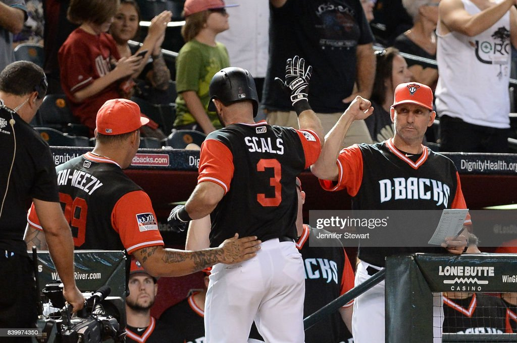 Daniel Descalso #3 of the Arizona Diamondbacks wearing a nickname-bearing jersey is congratulated by manager Torey Lovullo #17 after hitting a solo home run in the eighth inning against the San Francisco Giants at Chase Field on August 27, 2017 in Phoenix, Arizona.