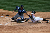 Daniel Descalso of the Colorado Rockies beats the tag and scores on a safety squeeze bunt from Tony Wolters as catcher Curt Casali of the Tampa Bay...
