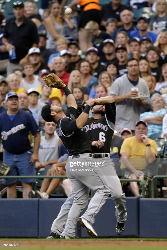 Daniel Descalso of the Colorado Rockies makes the catch in foul territory to retire Hernan Perez of the Milwaukee Brewers during the first inning at...