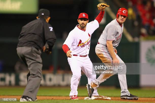 Daniel Descalso of the St Louis Cardinals and Jay Bruce of the Cincinnati Reds look to the second base umpire for a call at Busch Stadium on October...