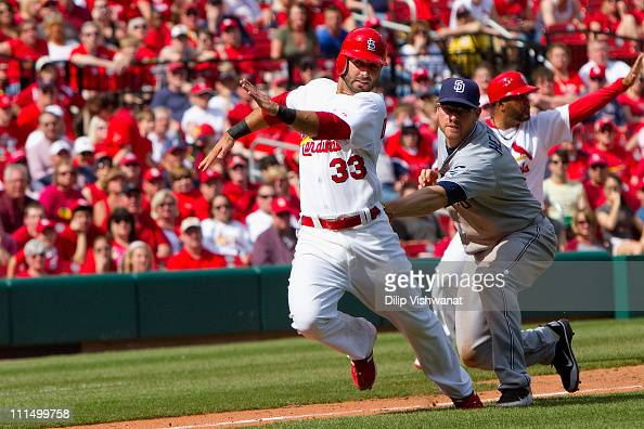 Daniel Descalso of the St Louis Cardinals is caught in a rundown by Chase Headley of the San Diego Padres at Busch Stadium on April 3 2011 in St...