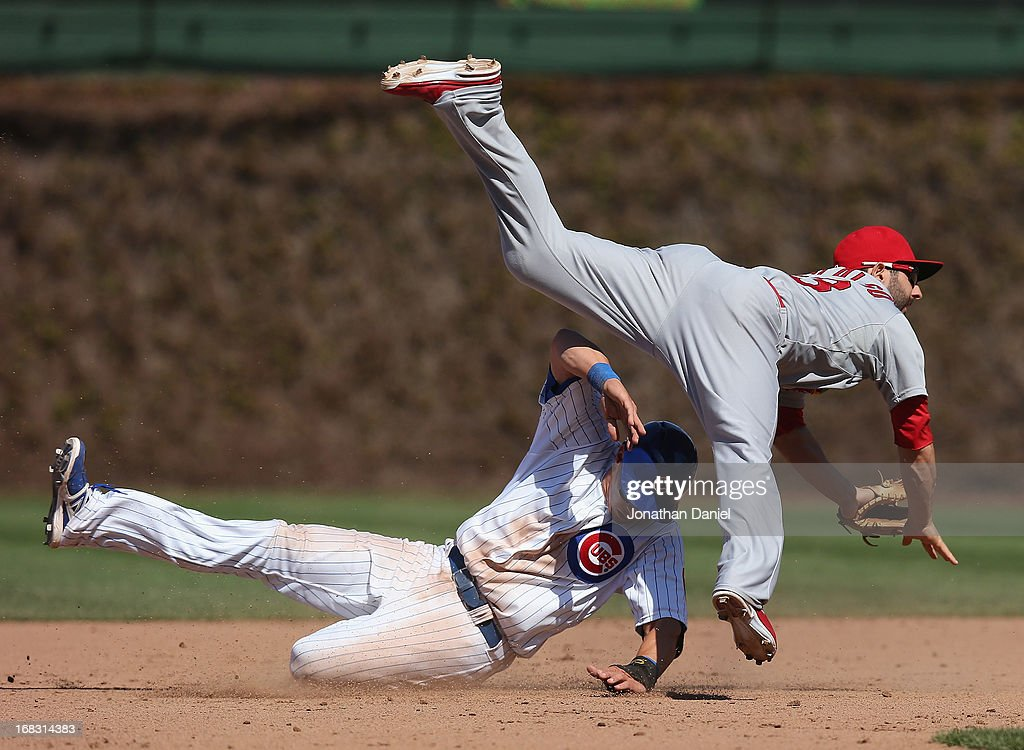Daniel Descalso #33 of the St. Louis Cardinals leaps over Cody Ransom #1 of the Chicago Cubs as he turns a double play in the 7th inning at Wrigley Field on May 8, 2013 in Chicago, Illinois.