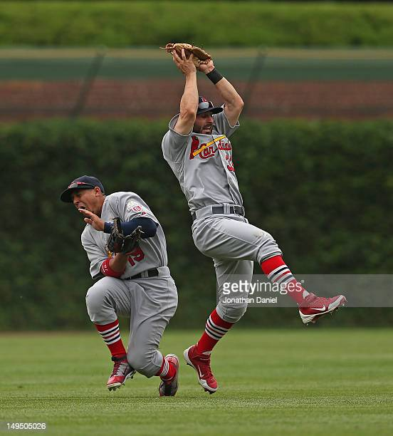 Daniel Descalso of the St Louis Cardinals makes a catch as teammate Jon Jay tries to avoid a collision against the Chicago Cubs at Wrigley Field on...