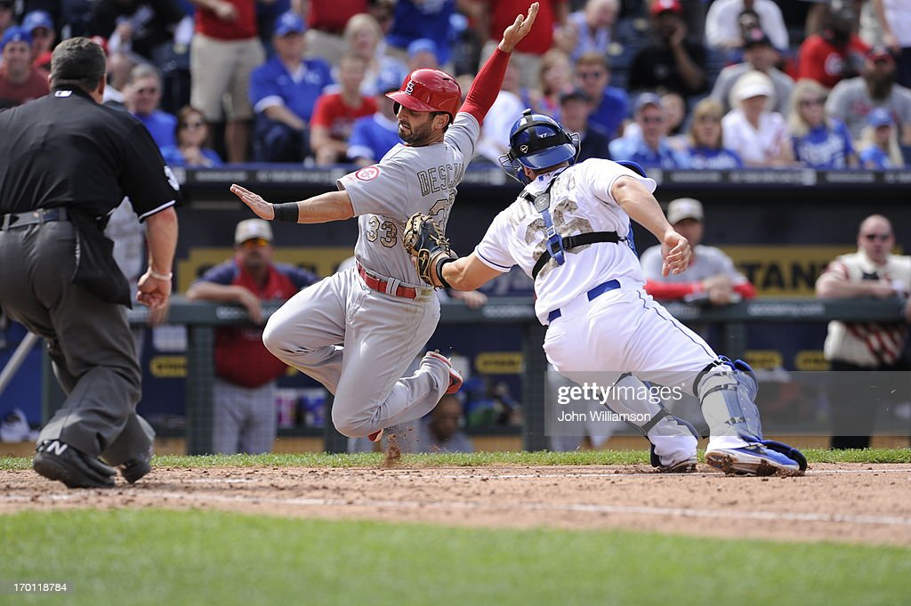Daniel Descalso of the St Louis Cardinals slides home safely to score a run as he avoids the tag of catcher George Kottaras of the Kansas City Royals...