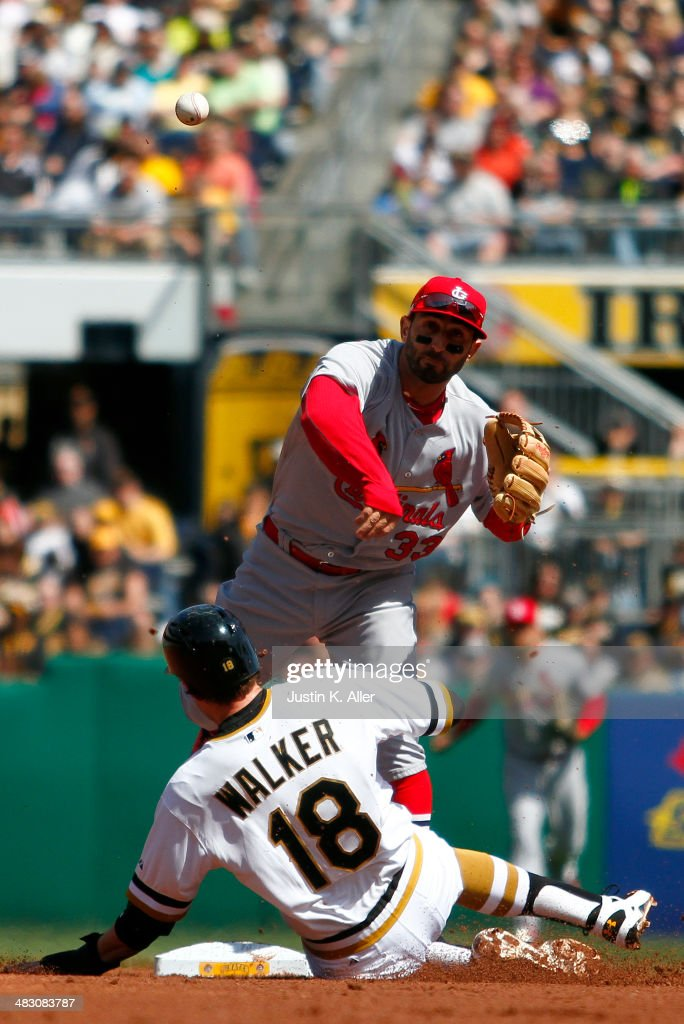 Daniel Descalso #33 of the St. Louis Cardinals turns a double play in the second inning against Neil Walker #18 of the Pittsburgh Pirates during the game at PNC Park April 6, 2014 in Pittsburgh, Pennsylvania.