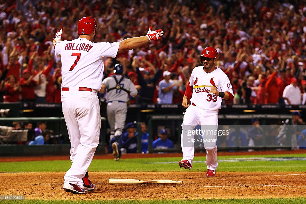 Daniel Descalso #33 scores the game winning run as Matt Holliday #7 of the St. Louis Cardinals greets him at home plate in the 13th inning against the Los Angeles Dodgers during Game One of the National League Championship Series at Busch Stadium on October 11, 2013 in St Louis, Missouri.