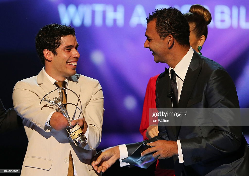 Daniel Dias (L) receives his award for 'Laureus World Sportsperson of the Year with a Disablity' from Laureus Ambassador <a gi-track='captionPersonalityLinkClicked' href=/galleries/search?phrase=Ruud+Gullit&family=editorial&specificpeople=2104975 ng-click='$event.stopPropagation()'>Ruud Gullit</a> during the awards show for the 2013 Laureus World Sports Awards at the Theatro Municipal Do Rio de Janeiro on March 11, 2013 in Rio de Janeiro, Brazil.