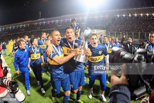 Daniel Diaz and Andres Chavez of Boca Juniors lift the trophy after winning a final match between Boca Juniors and Rosario Central as part of Copa...